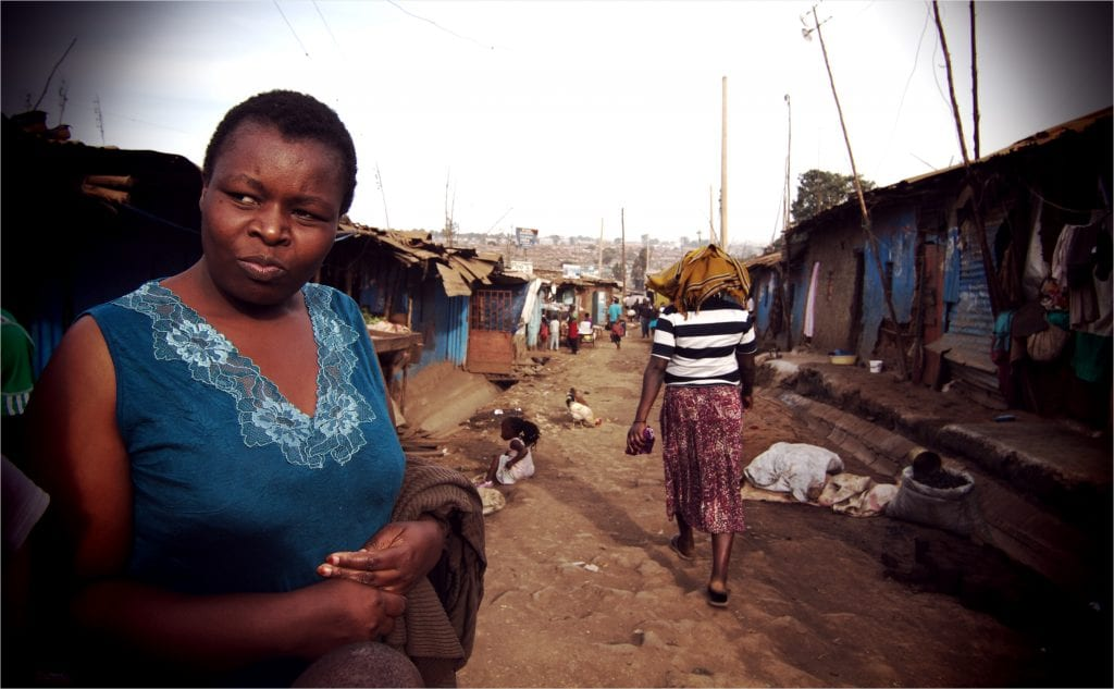 Helen waits for her two children as she walks a main pathway through the Kibera slums.