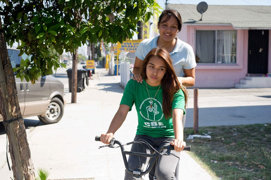 Actresses Fenessa Pineda And Venecia Troncoso As Characters Yolanda And Mari Riding A Bike Together.