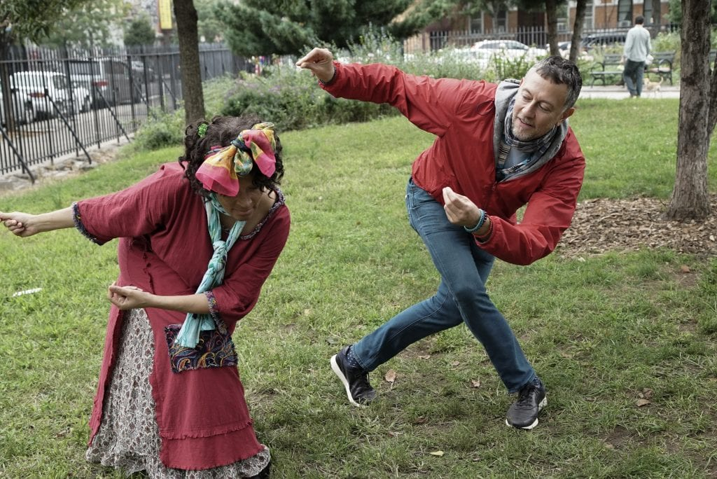 A woman imitating a man's dancing in a park