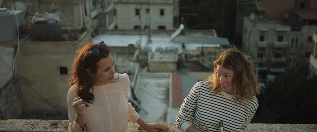 Two women looking playfully at each other with short urban buildings off the balcony behind them