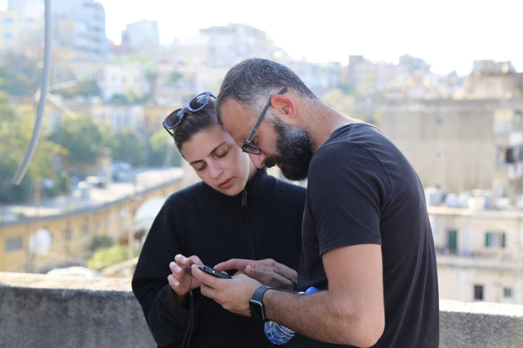 A man and woman looking at a phone with a skyline in the background
