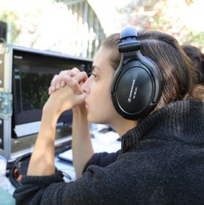 A woman wearing headphones looking at a screen