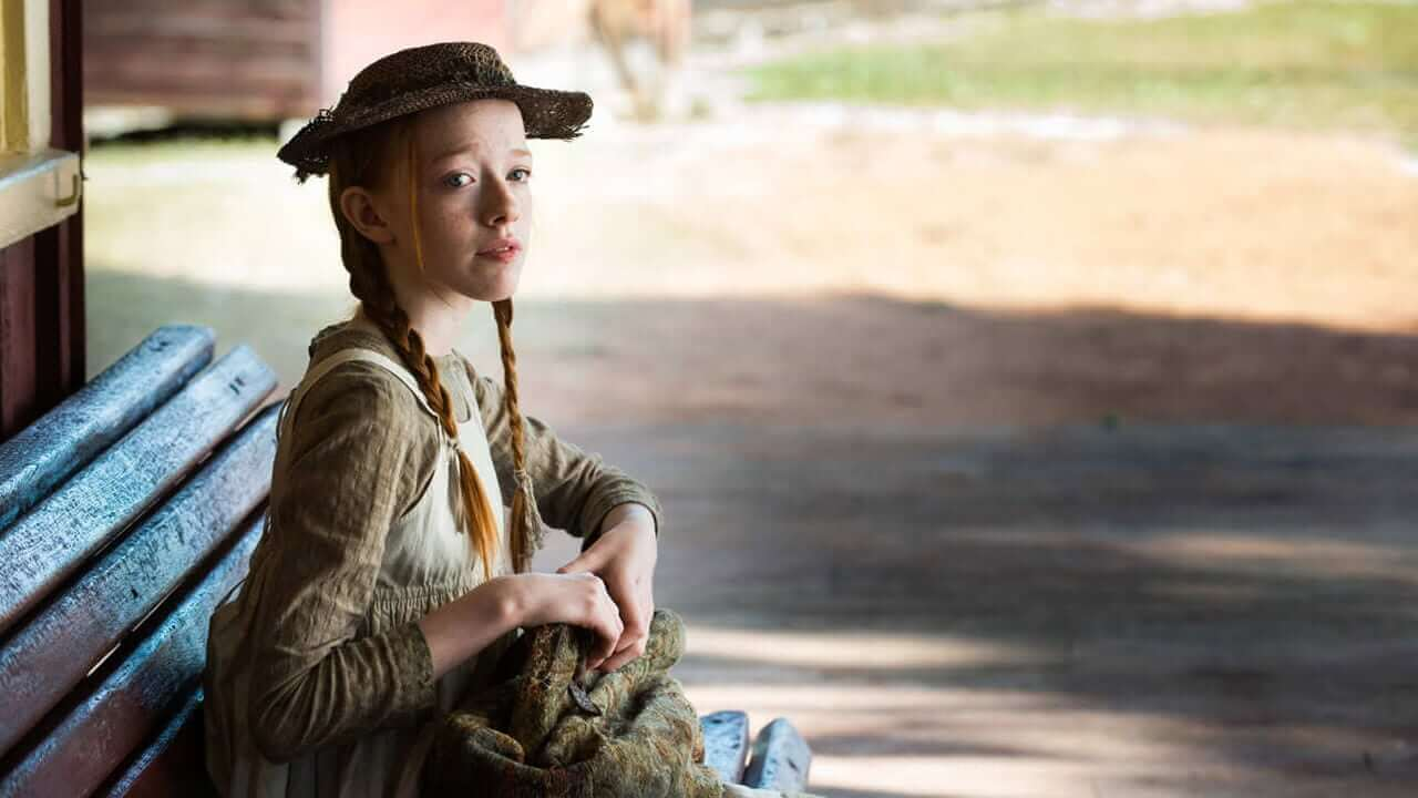 Actress Amybeth McNulty who is playing Anne Shirley is wearing a green dress and sitting on a bench.