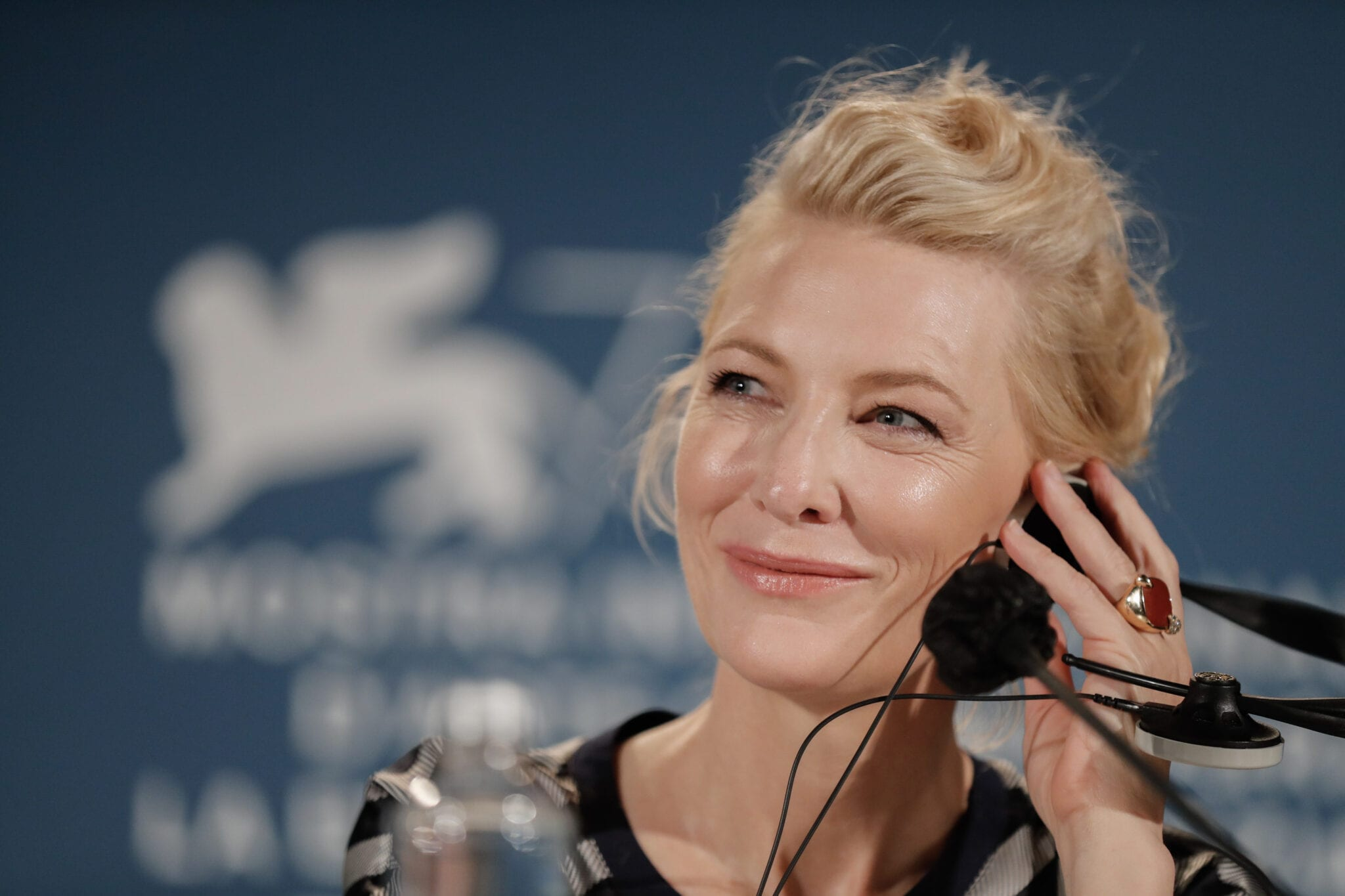 Cate Blanchett smiles and looks to the left while holding a black headset to her ears.