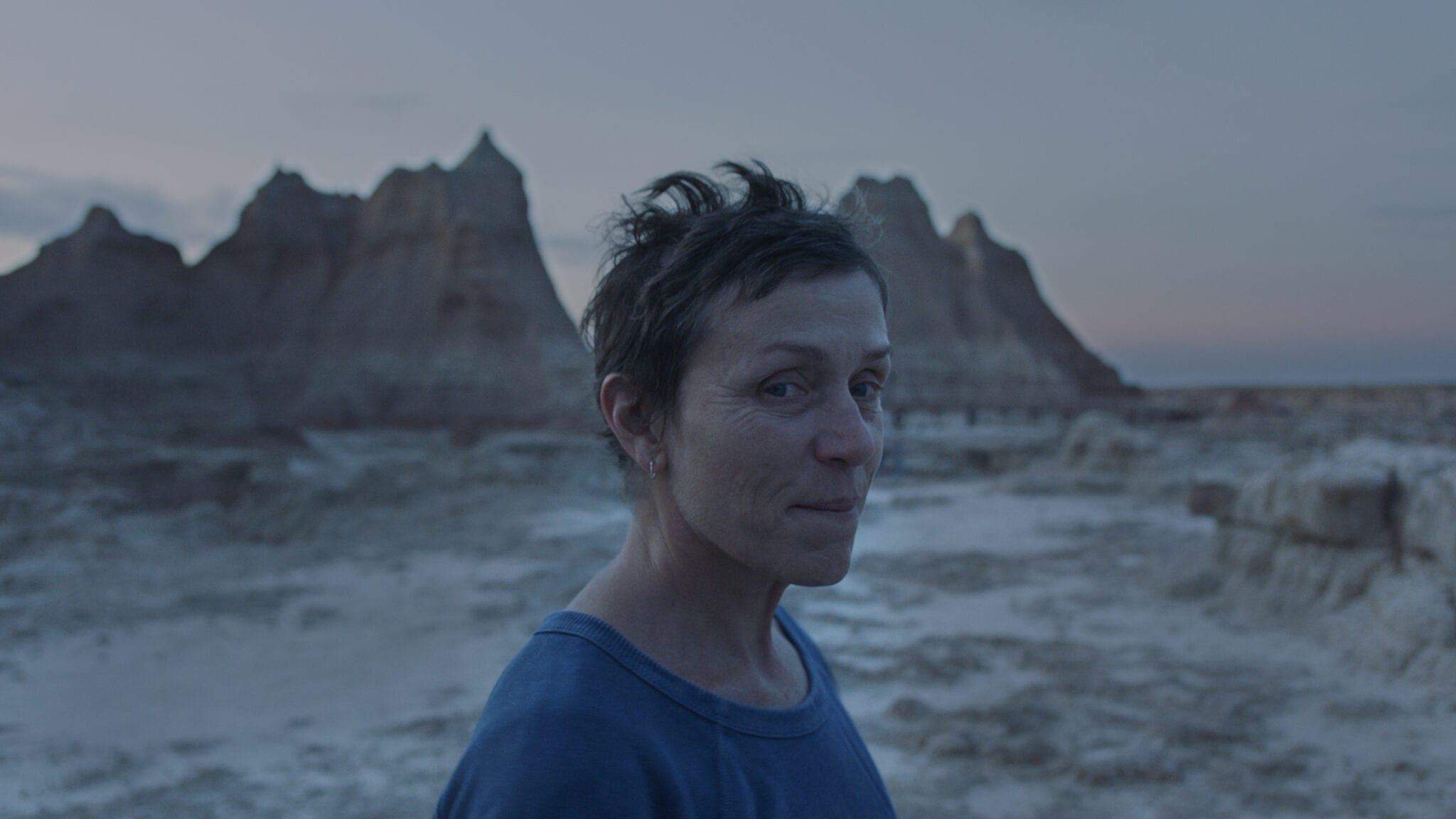 Mcdormand wearing a blue t-shirt looking towards the camera while standing in front of a mountainous background.