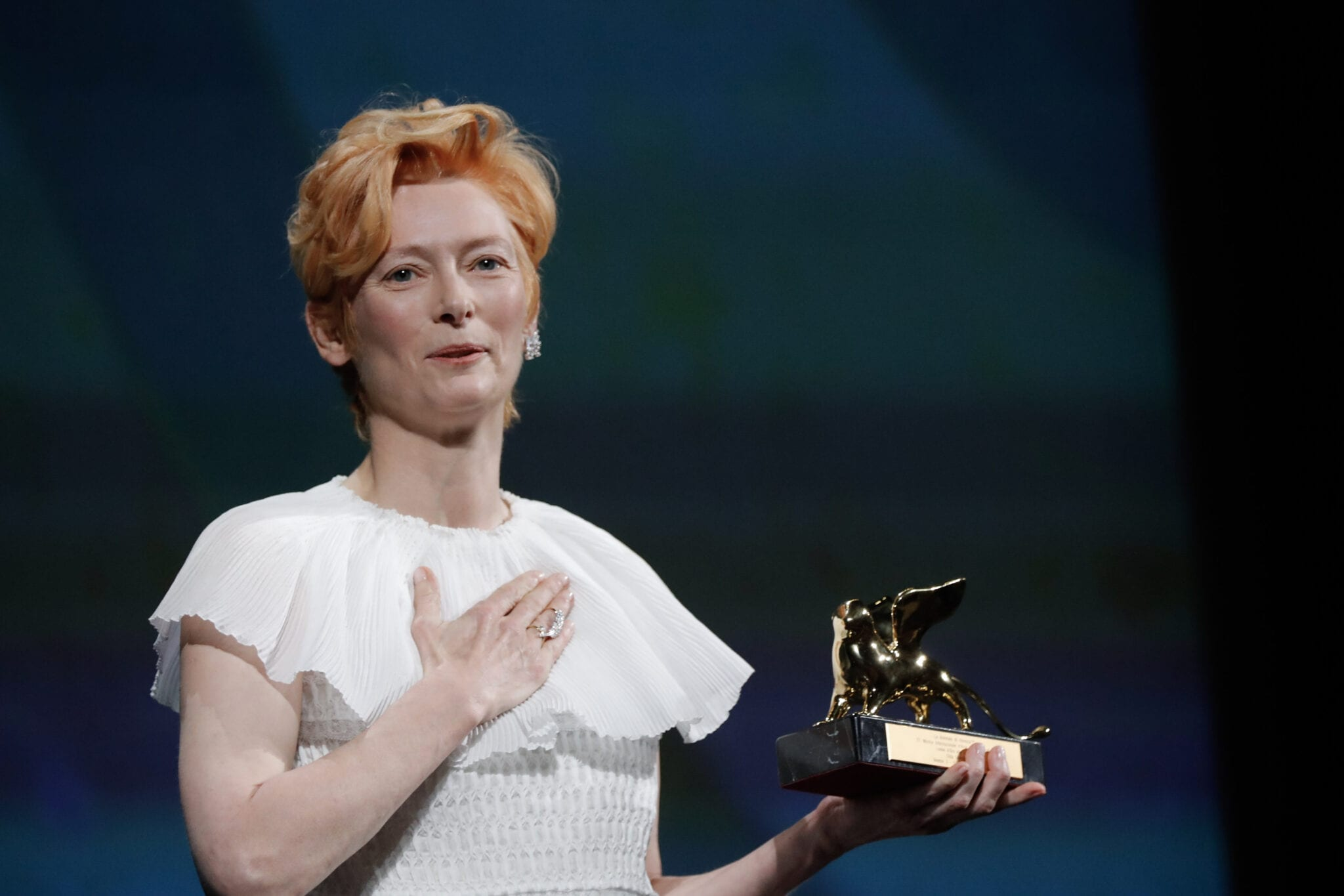 Swinton wears a white dress and holds the Golden Lion statue in one hand with her other hand pressed to her heart.