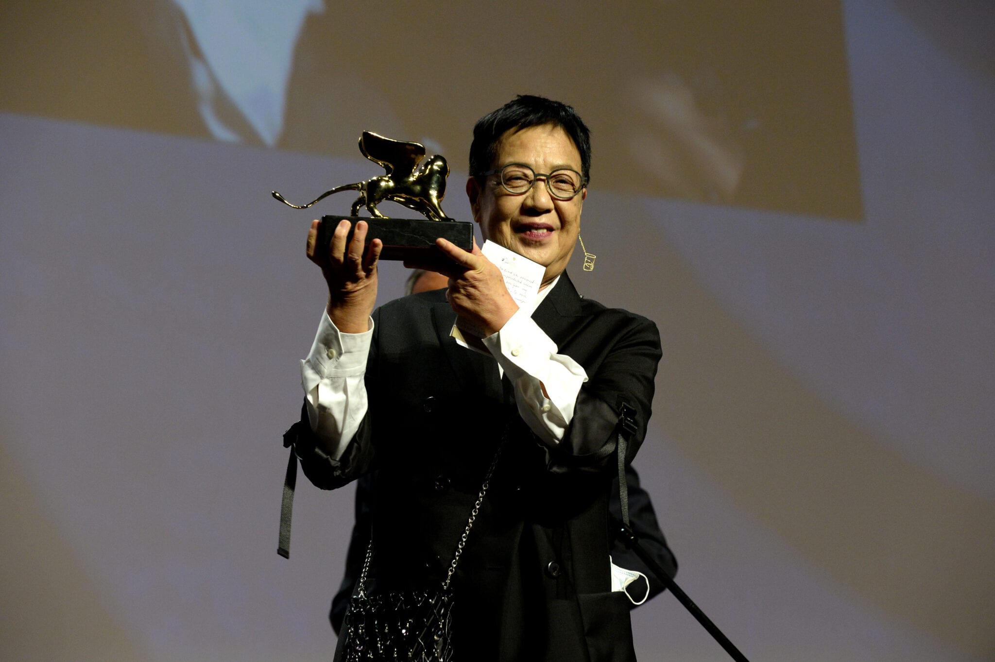 Ann Hui Holds Her Golden Lion Award While Wearing A Black Jacket.