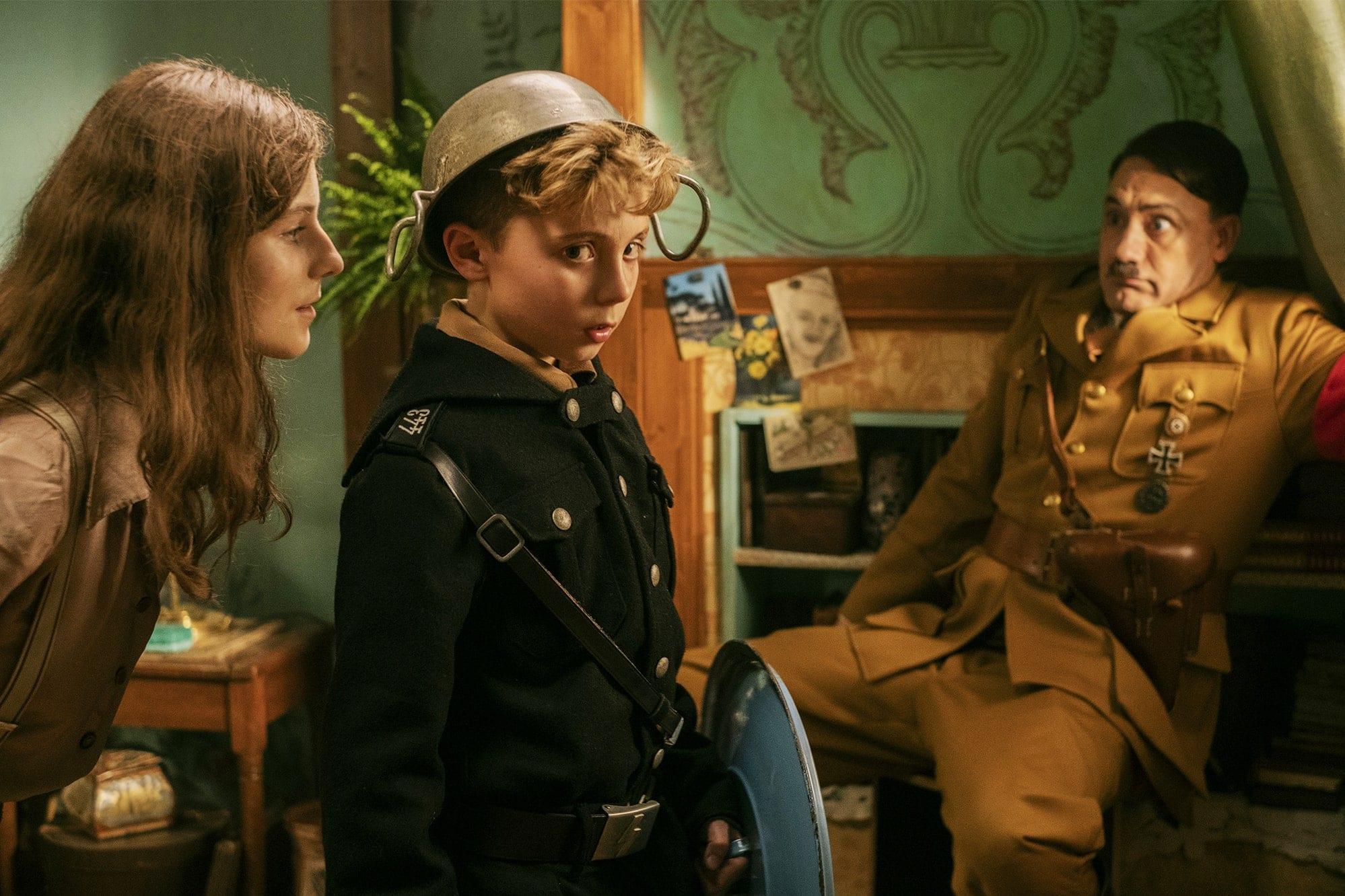 Elsa leans to whisper in Jojo's ear, as imaginary Hitler cowers in the corner.