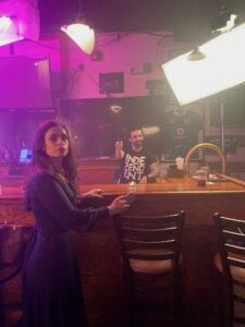 Zannou stands in the foreground of the bar wearing a blue dress. Alicia is behind the bar in a t-shirt. Large set lights are in the upper right of the image.