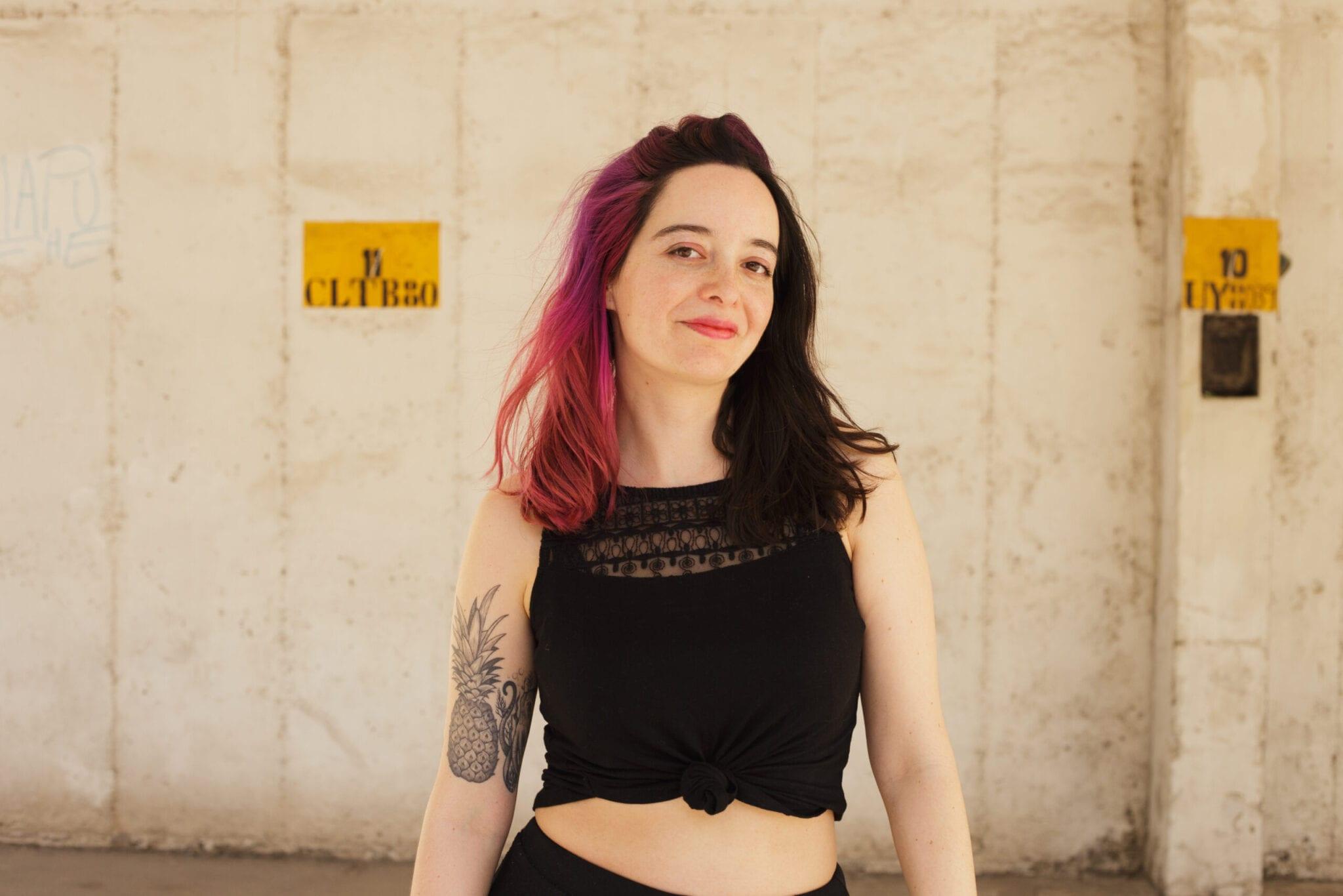 Headshot Of María Carolina Quintana. She Has Pink Hair And Is Wearing A Black Shirt.