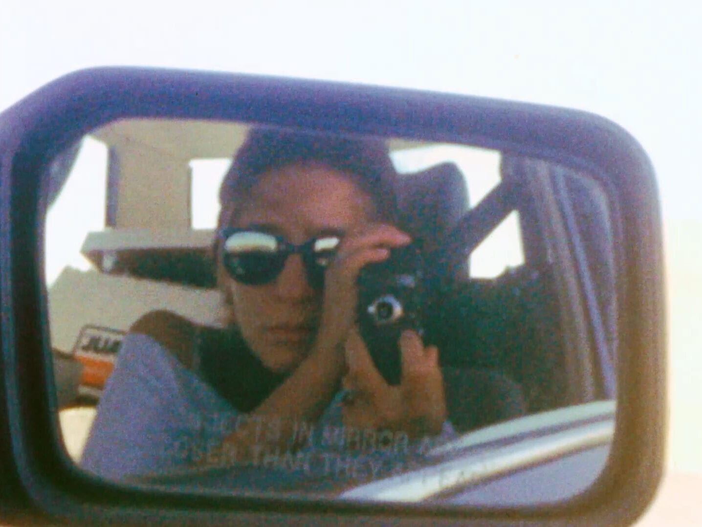 Still From Lynne Sachs' Film About A Father Who. Lynne Is Holding A Camera In Front Of Her Face And Is Reflected In A Car's Side Mirror.