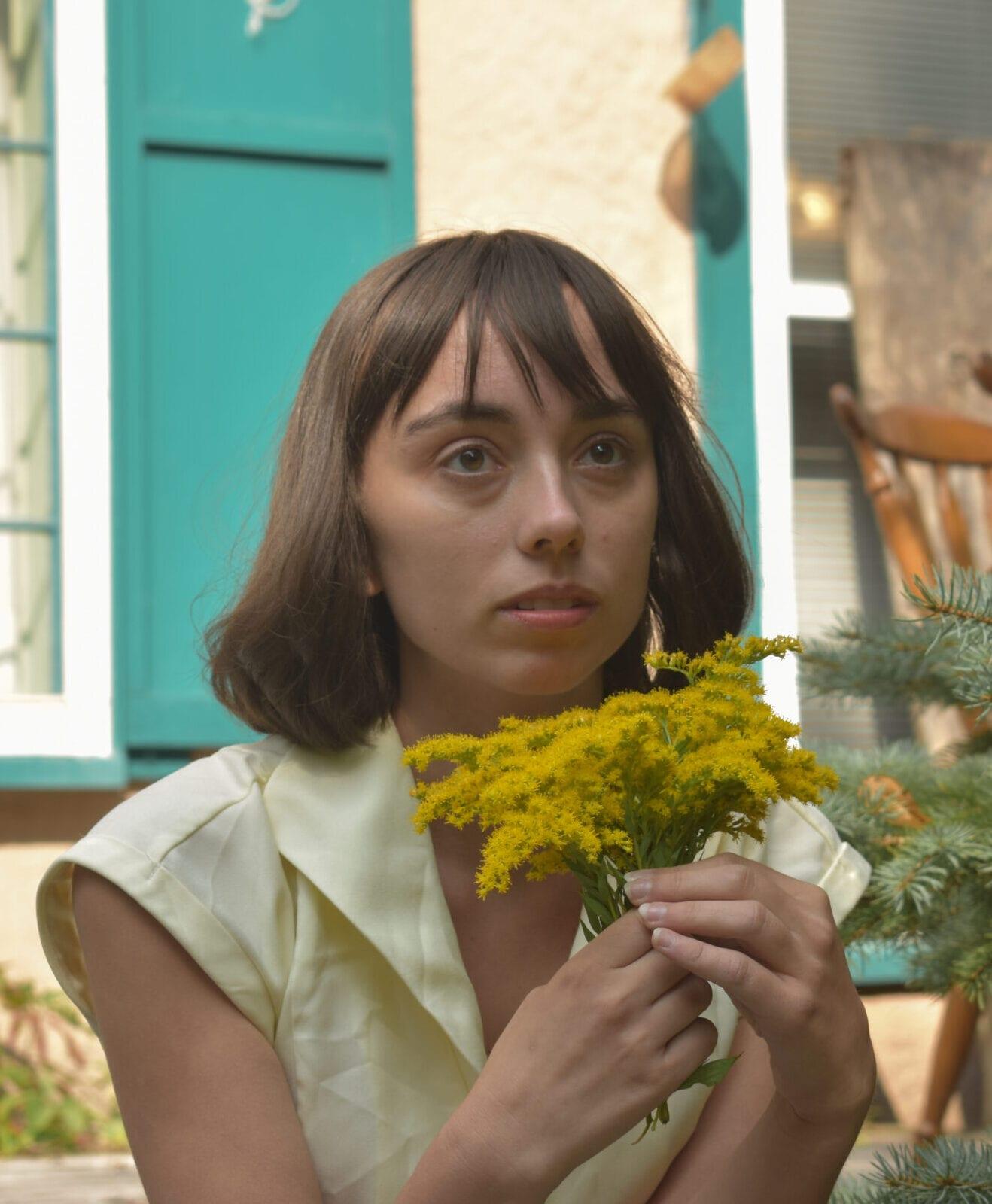 Image Of Ellie Wells, Director Of Eagle Rock, Holding Some Flowers.