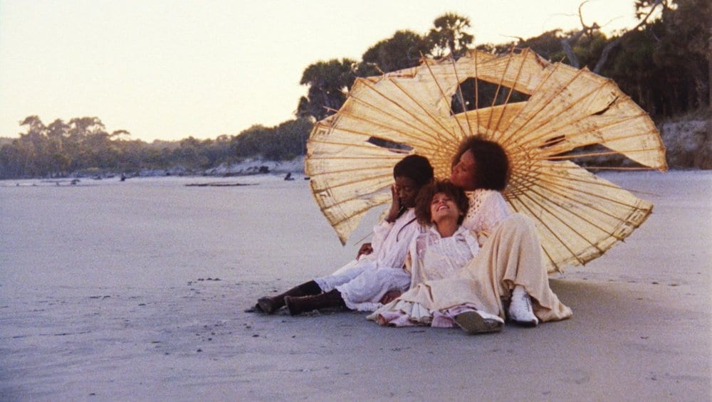 Still from Daughters of the Dust with girls sitting on a beach under an umbrella
