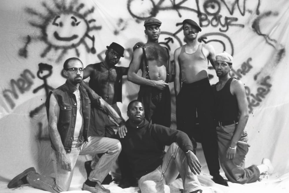 A still from Tongues Untied with a bunch of men in front of a graffitied wall
