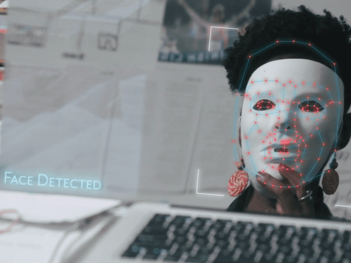 "An image of Buolamwini sitting in front of a screen and keyboard, holding up a white mask in front of her face. The text ""face detected"" is visible at the bottom of the screen. A constellation-esque map of blue lines and red dots is superimposed on top of her masked face."