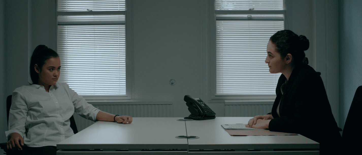 Still of Mallory and Jenny in the interrogation room. It is a dimly lit room with two windows with the blinds pulled, and a table the two characters are sitting at with a landline phone on it. Almost everything in the room is white. Jenny is staring down Mallory while slouching a bit in her chair.