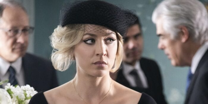 A close up of Cassie dressed in funeral garb (including a vintage-style hat with netting on it) looking off to the side while other funeral attendees stalk behind her.