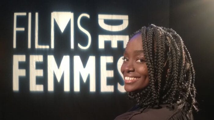 """An image of Aïssa Maïga sitting in a black, folding director's chair with """"films de femmes"""" written on the back. She is a black room with a light up sign of """"films de femmes."""""""