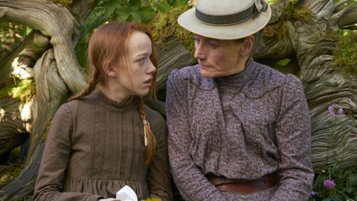 Anne and Marilla are sitting on a log together, looking at each other seriously as they discuss something. They are both dressed in simple historical clothing. Anne's hair is messy while Marilla is wearing a hat.