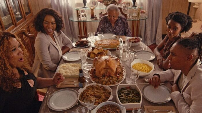 Catherine and Denise's family (five total people) sit around a heavily-laden thanksgiving table in an older-looking house. They all have big, happy expressions on their faces.