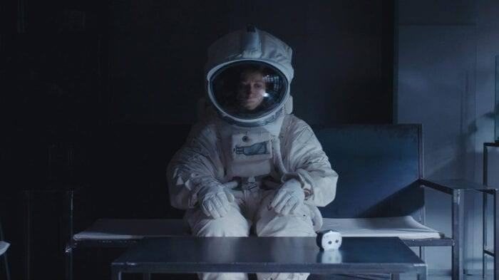 Eva is sitting in a darkened, sparse, modern living room wearing a spacesuit and staring off at the ground.