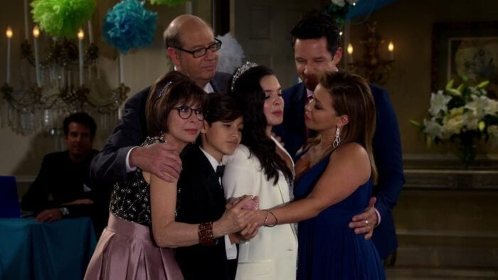 Elena is standing in the center of a dance floor, wearing a white suit and tiara, surrounded by her family in a sort of group hug (they are all earing formal wear).