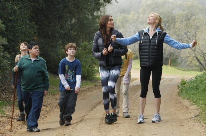 Gloria and Claire smile and talk with their hands as they walk on a nature trail with four of their children. The moms are dressed in athleisure clothing with puffer jackets, while the kids look incredibly bored and are dressed in neutral, junky clothes.