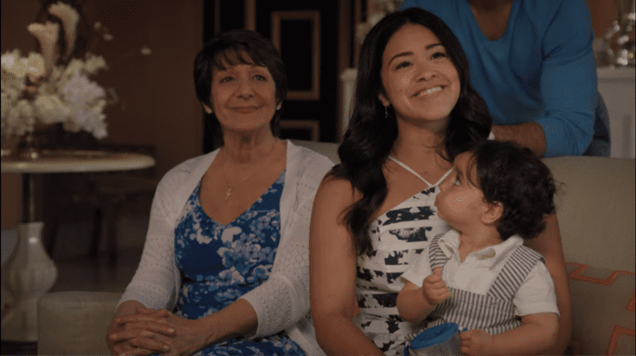 Gina and her abuela are looking up and smiling at something. Gine hold her son, who is clearly not paying attention. They are all dressed in light-colored, slightly formal clothing.