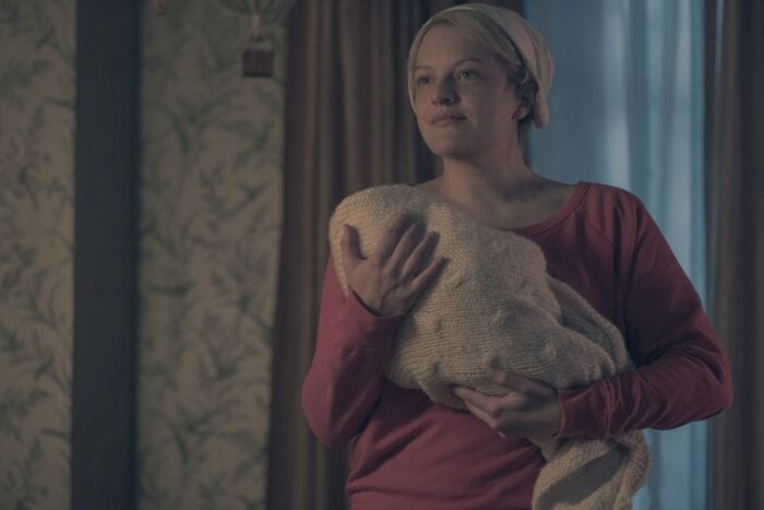 Jane, wearing a white cap and red outfit, smiles and looks over at something while holding a swaddled baby in a beige, textured blanket.