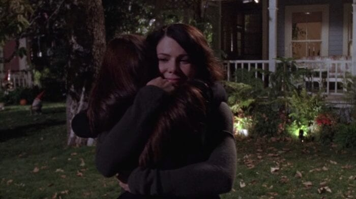 Lorelai and Rory hug each other outside of someone's house on an autumn evening. They are both wearing dark, long sleeve shirts.