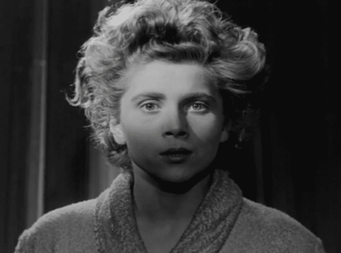 A black and white image of Nicole Stéphane wearing a bathrobe and looking at the camera in a slightly shocked way.