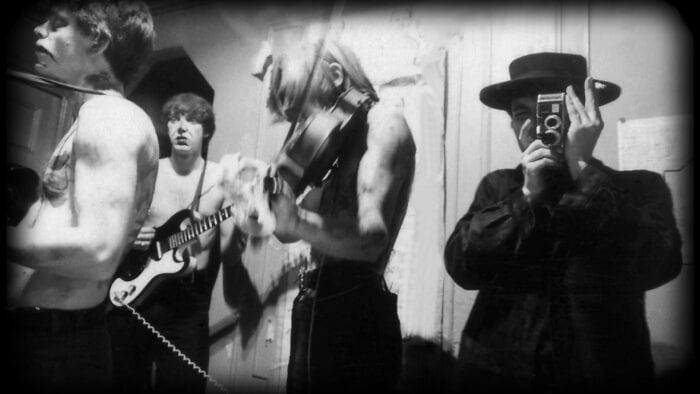 A black-and-white image of Piero Heliczer holding a camera up to his face with members of the velvet underground busily moving around with instruments.