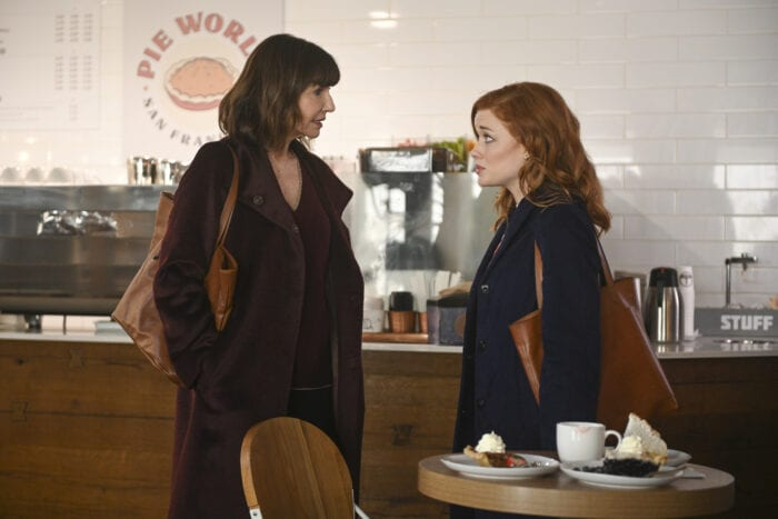 Zoey and her mother look at each other seriously as they have a conversation in a clean, modern coffee shop. They are both dressed for the fall/winter.