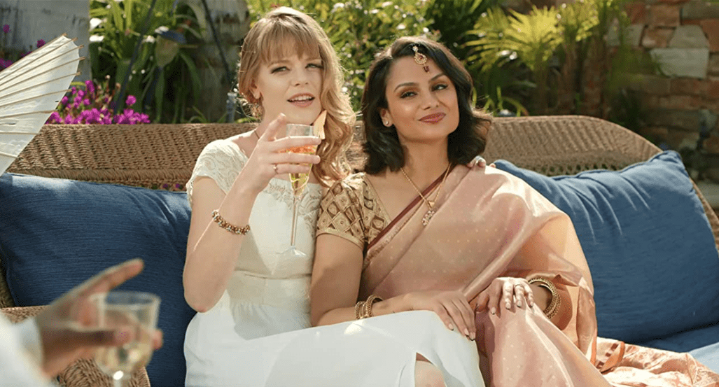 Savarna and Charley sit together on an outdoor couch. They are both looking over at someone. Charley is wearing white and holding a champagne flute; Savarna is wearing west Asian pink clothing, her hand resting on Charley's leg.