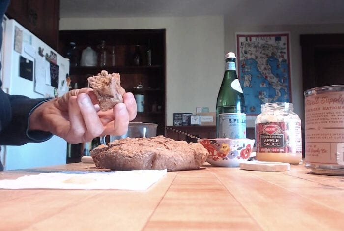 Still from the film of a woman's hands pulling apart bread to eat. She is standing at a wooden kitchen counter where there are a variety of containers and bowls for foods like sparking water and applesauce.