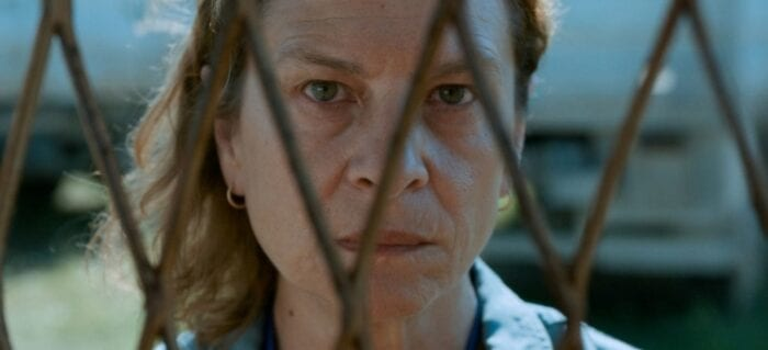 A still of a woman looking through a fence at the camera. Her face looks hardened by time.