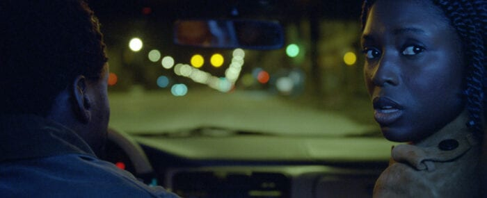 From the backseat of a car, we see Queen looking behind her with Slim in the driver's seat, their faces illuminated by the blue lights of  a cop car.