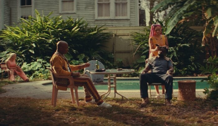 Slim and Uncle Earl are seated outside in plastic chairs. A girl is doing Slim's hair as the two talk.