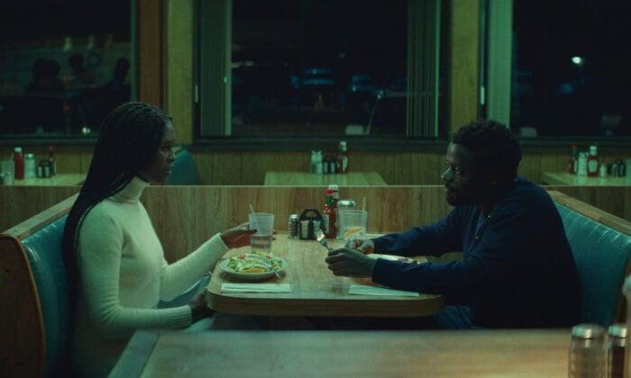 Queen and Slim are seated at a booth in a dingy-looking restaurant late at night, talking over cups of water and a sad-looking salad.