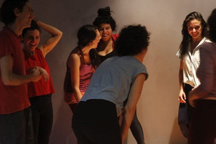 Avila stands with a group of dancers in a dimly lit set, smiling and laughing between takes.