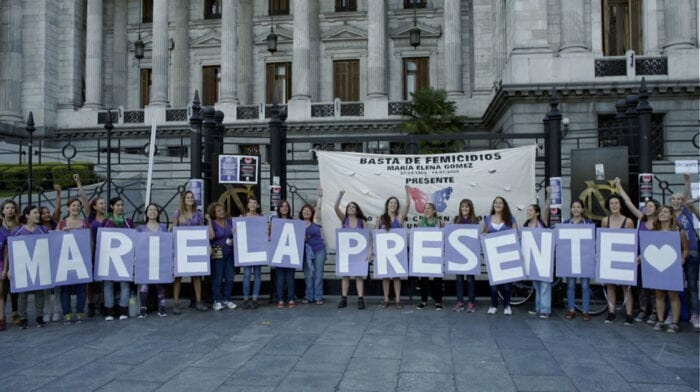 """Women stand in a line outside of what appears to be a government building, holding up large lettered signs that spell """"Mariela Presente."""""""