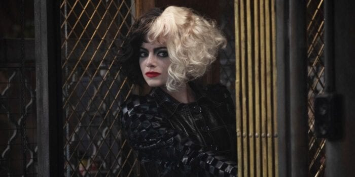 Cruella (Emma Stone) peers around a corner of a metal fence, wearing a textured pleathered jacket.